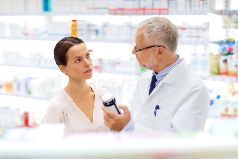 Apotheker en vrouw met drug bij apotheek stock afbeelding