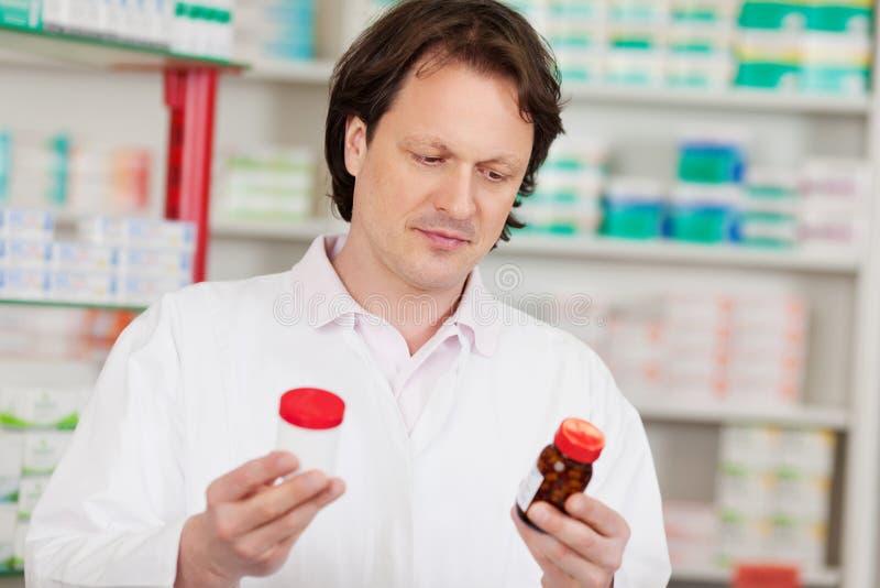 Apotheker Holding Pill Bottles in der Apotheke lizenzfreies stockbild