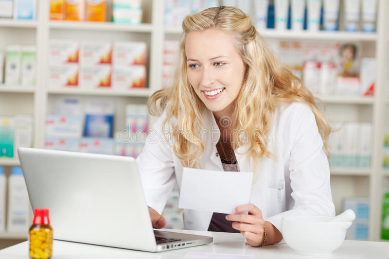 Apotheker Holding Prescription While die Laptop met behulp van in Coun stock fotografie