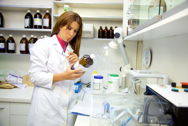 Apotheker in laboratorium die aan geneeskunde werken die resultaten controleren stock afbeeldingen