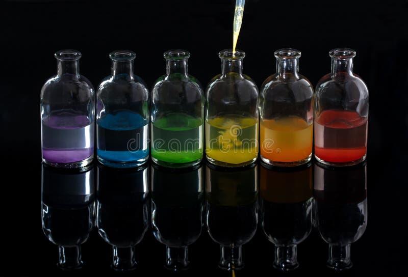 Apotheker, laboratoriumflessen met gekleurde vloeistof en pipet royalty-vrije stock foto