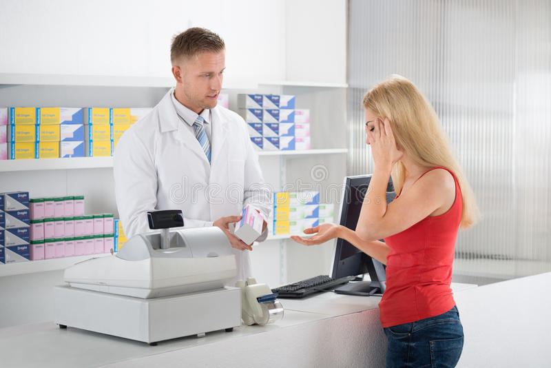 Apotheker Looking At Customer die aan Hoofdpijn lijden royalty-vrije stock afbeelding