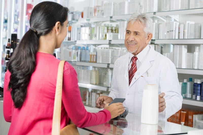 Apotheker Looking At Female, das NFC-Zahlung für Shampoo leistet stockfotografie