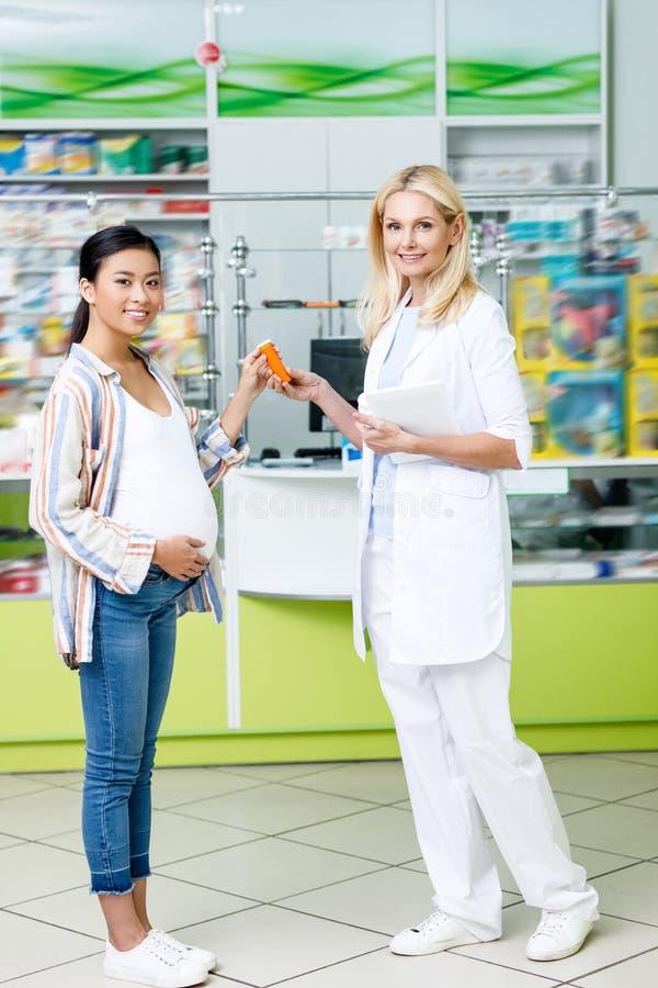 apotheker met digitale tablet en zwanger klantenholding medicijn en het glimlachen stock afbeeldingen