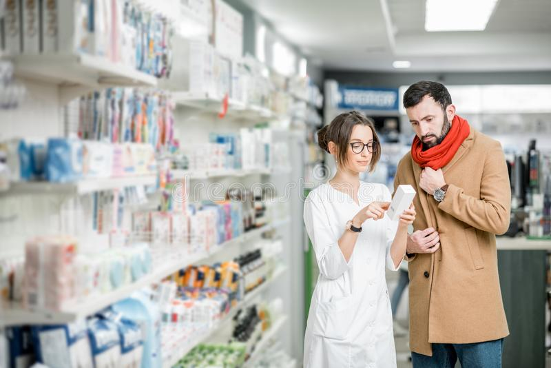Apotheker mit Kunden im Apothekenspeicher lizenzfreies stockbild