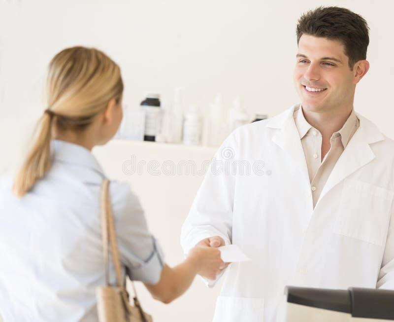 Apotheker Receiving Prescription Paper vom Kunden am Speicher lizenzfreie stockbilder