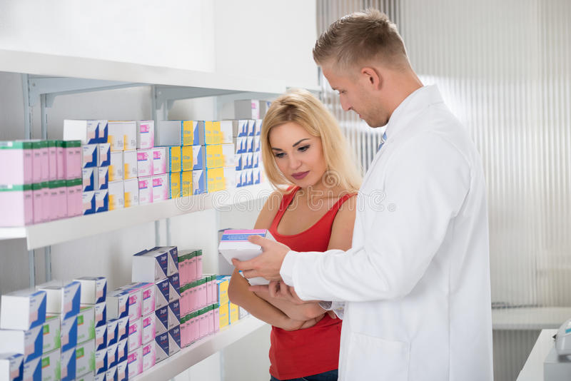 Apotheker Showing Medicine Box zum Kunden lizenzfreie stockbilder