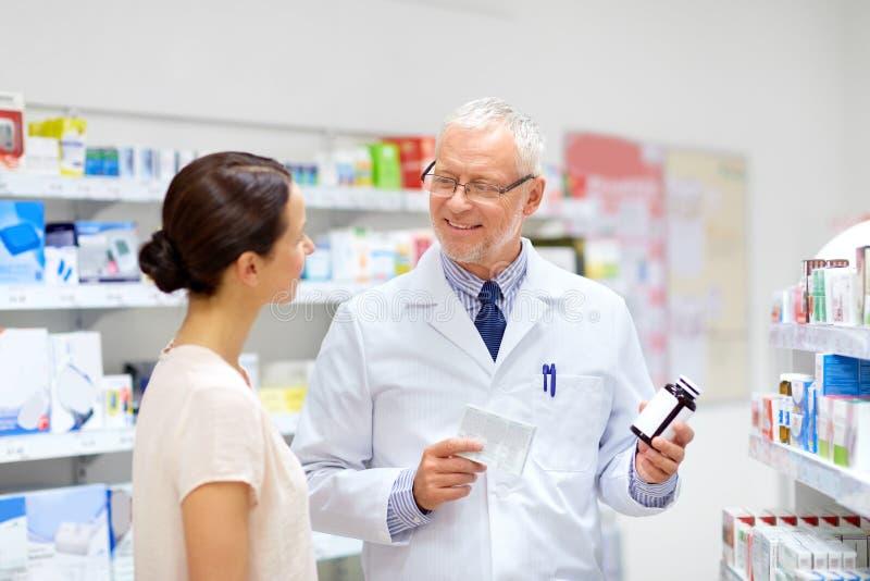 Apotheker und Frau mit Droge an der Apotheke lizenzfreies stockfoto