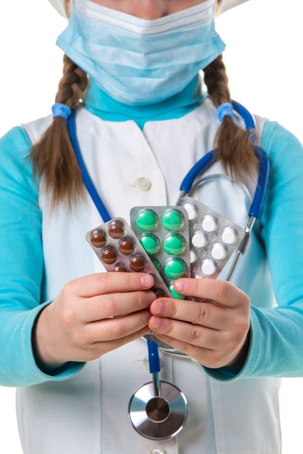 Apotheker weiblich in der weißen Robe und in der madical Maske, stathoscope, das viele bunten Pillen und Tabletten im Paket, Absc lizenzfreie stockfotografie
