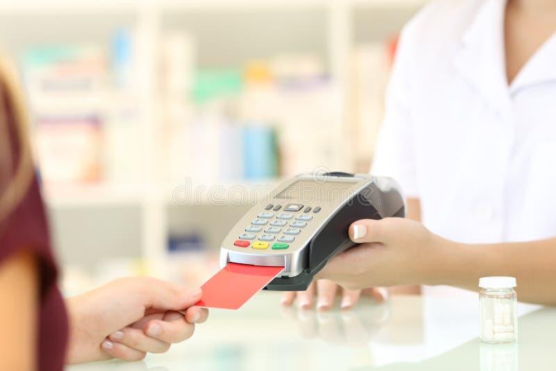 Apothekerhände, die mit Kreditkartenleser aufladen stockfoto