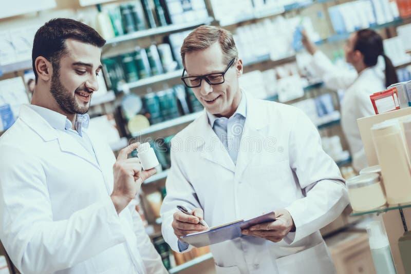 Apothekers die in apotheek werken stock afbeelding