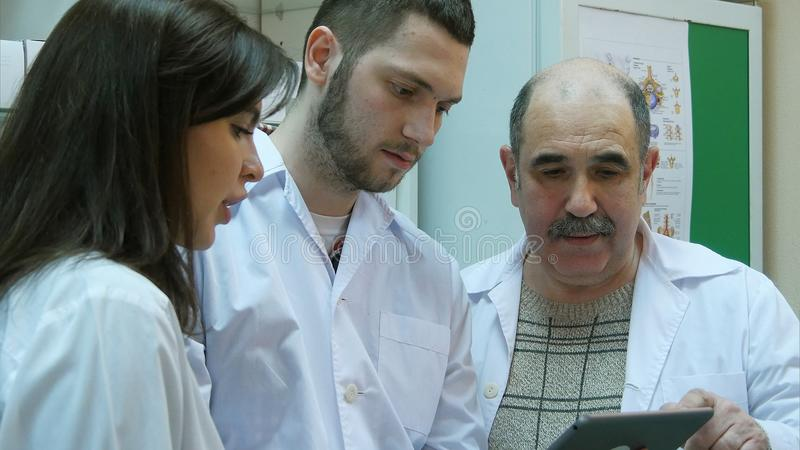 Apothekers die digitale tablet gebruiken terwijl het controleren van geneeskunde in apotheek stock foto's