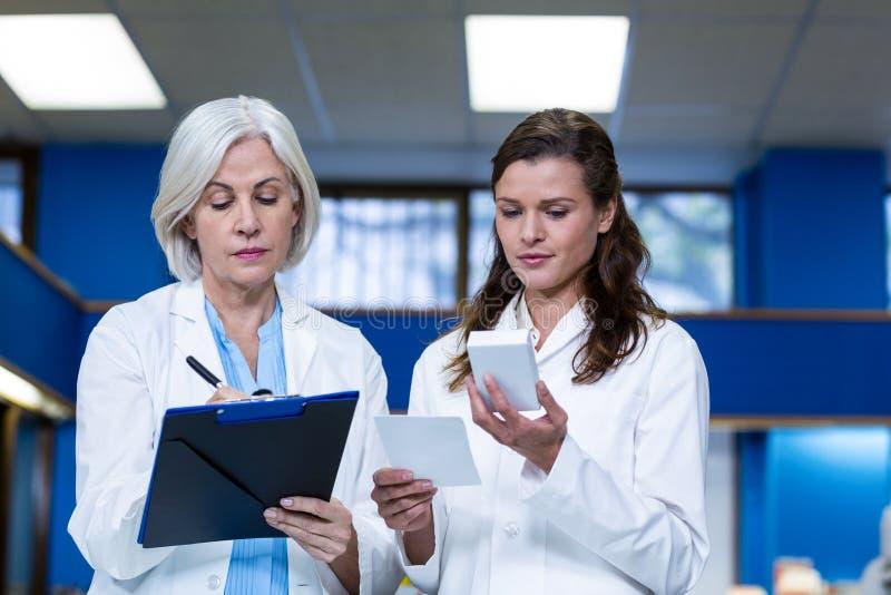 Apothekers die en voorschrift controleren schrijven voor geneeskunde stock afbeeldingen