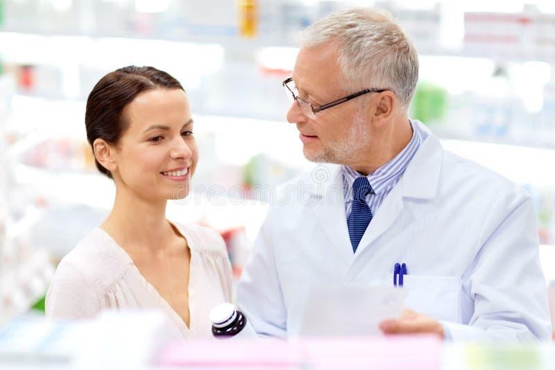Apothicaire et femme avec la drogue ? la pharmacie image stock