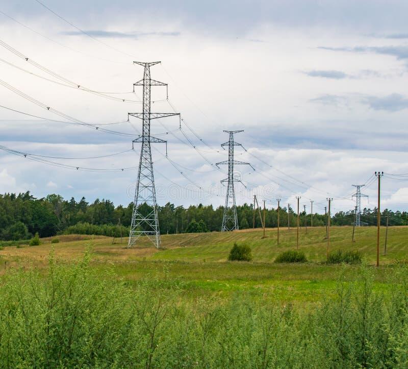 Apoya líneas eléctricas de alto voltaje contra el cielo azul con las nubes Industria eléctrica imagenes de archivo