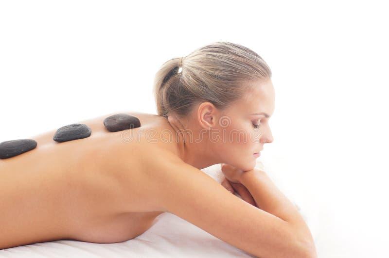 Apoye a una mujer joven que pone en un masaje de la piedra de la lava imagen de archivo libre de regalías