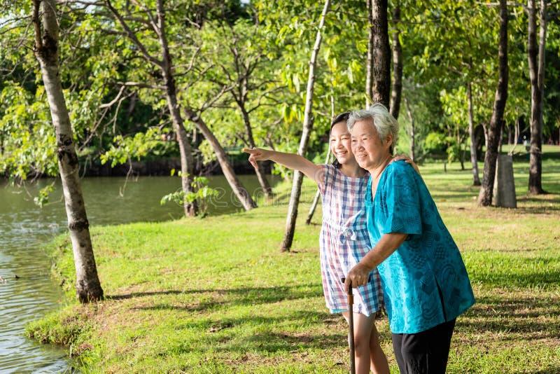 Apoyo asiático de la niña, mirando algo mujer mayor con el bastón, abuela sonriente feliz, nieta en al aire libre fotografía de archivo libre de regalías