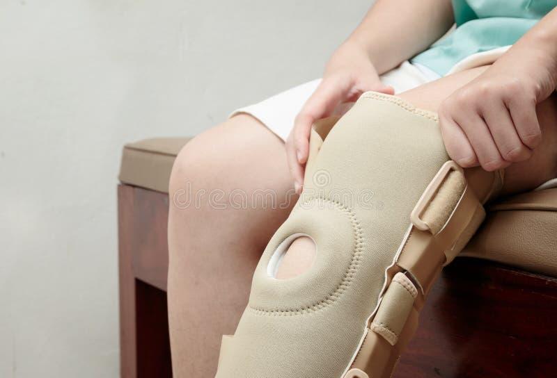 Apoyo de rodilla elástico herido de la mujer que lleva en cente de la rehabilitación imagenes de archivo
