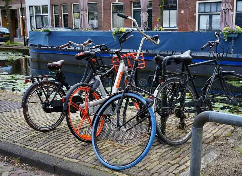 Different types of bikes at Delft, The Netherlands; Mobike, Swapfiets and normal bicycles. App, bicycle, bike, biking, blue tire, blue wheel, city, dutch royalty free stock photo