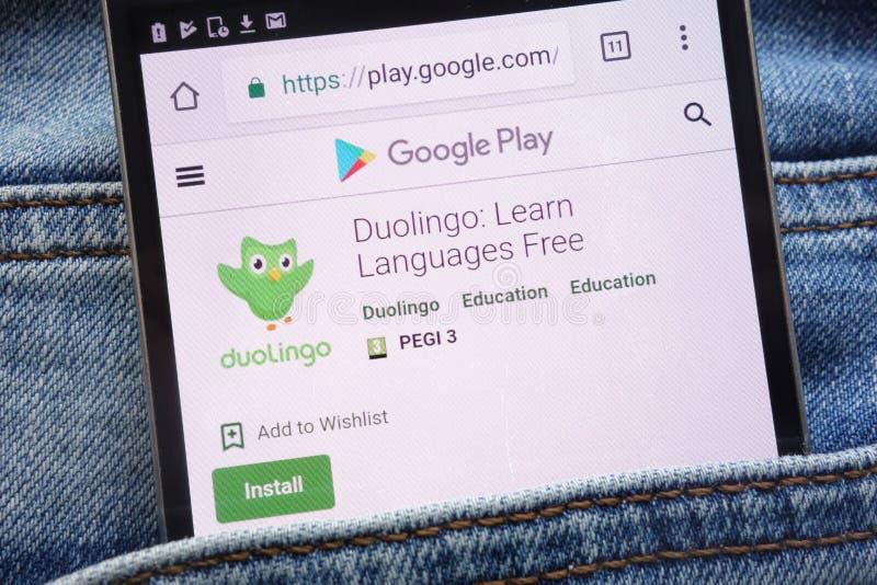 App de Duolingo en la página web de Google Play exhibida en smartphone ocultado en bolsillo de los vaqueros fotografía de archivo