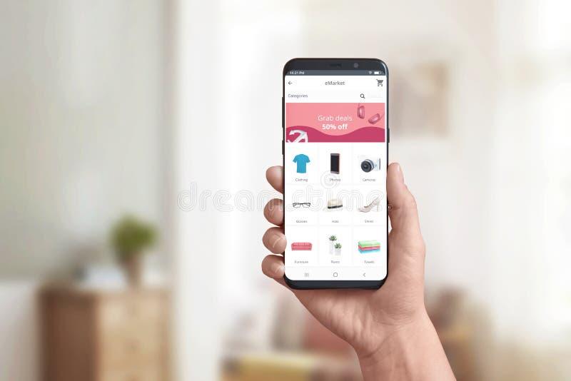 App de la tienda en línea de la demostración de la mano en un teléfono elegante moderno Concepto de tratos en línea de las compra imagen de archivo libre de regalías