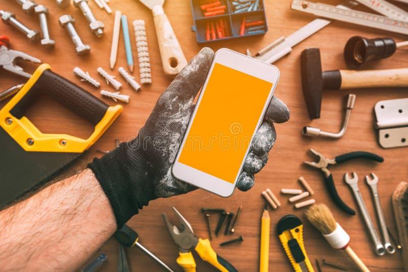 App del smartphone de la manitas, reparador que sostiene el teléfono móvil a disposición imágenes de archivo libres de regalías