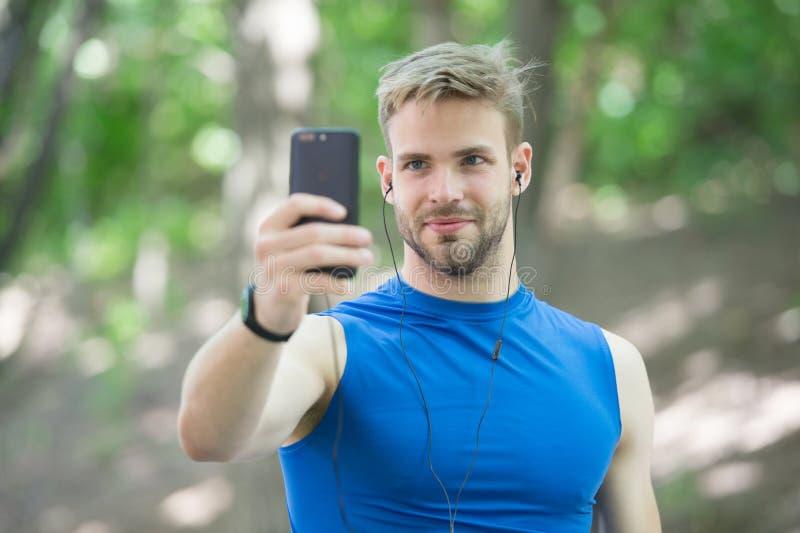 App do esporte no telefone esporte digital Rel?gio esperto o homem atlético no sportswear faz o selfie Exerc?cio ao ar livre Apti fotos de stock