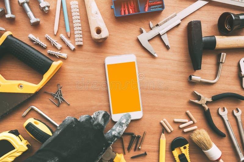 App elegante del teléfono de Handyperson, reparador que sostiene el teléfono móvil en h fotos de archivo