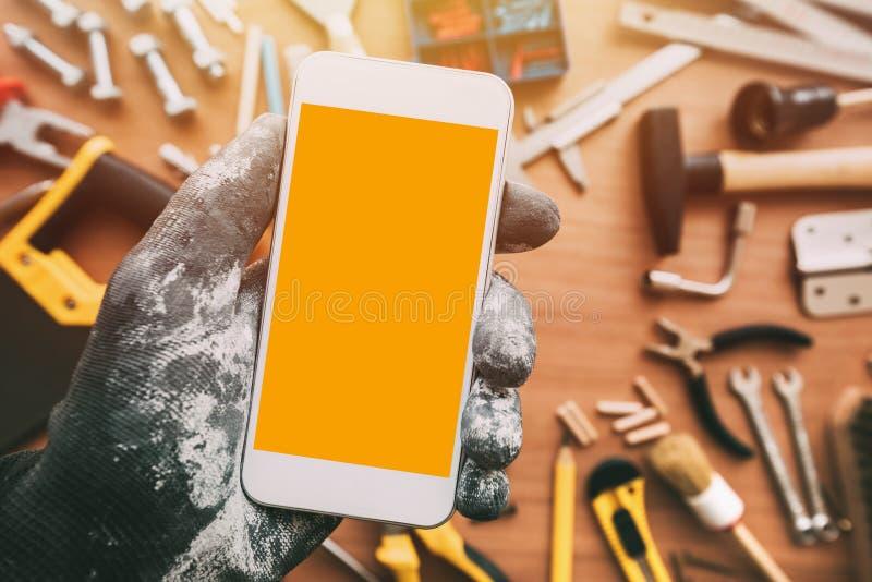 App elegante del teléfono de Handyworker, reparador que sostiene el teléfono móvil en h fotos de archivo libres de regalías