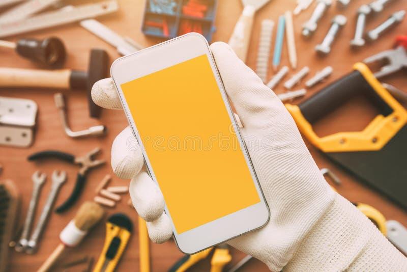App elegante del teléfono de la manitas, reparador que sostiene el teléfono móvil a disposición imagen de archivo