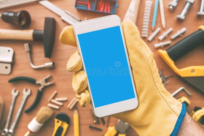 App elegante del teléfono de la manitas sobre el escritorio con las herramientas imagen de archivo libre de regalías