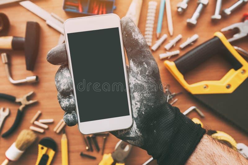 App elegante del teléfono para la manitas, reparador que sostiene el teléfono móvil fotografía de archivo
