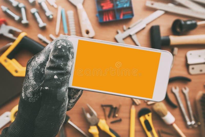 App elegante del teléfono del reparador, reparador que sostiene el teléfono móvil en Han imagen de archivo libre de regalías