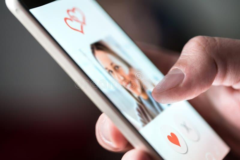 App que fecha en línea en smartphone Hombre que mira la foto de la mujer hermosa imagenes de archivo
