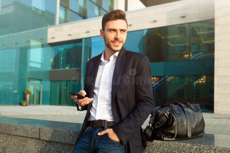 使用智能手机的年轻都市专业人 拿着流动智能手机的商人使用应用程序短信的sms消息佩带的夹克 免版税库存图片