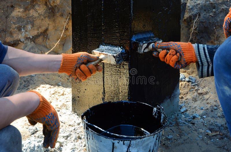 Appaltatore che dipinge il catrame o il bitume di carbone nero alla superficie di calcestruzzo dalla spazzola, un fondamento che  fotografia stock