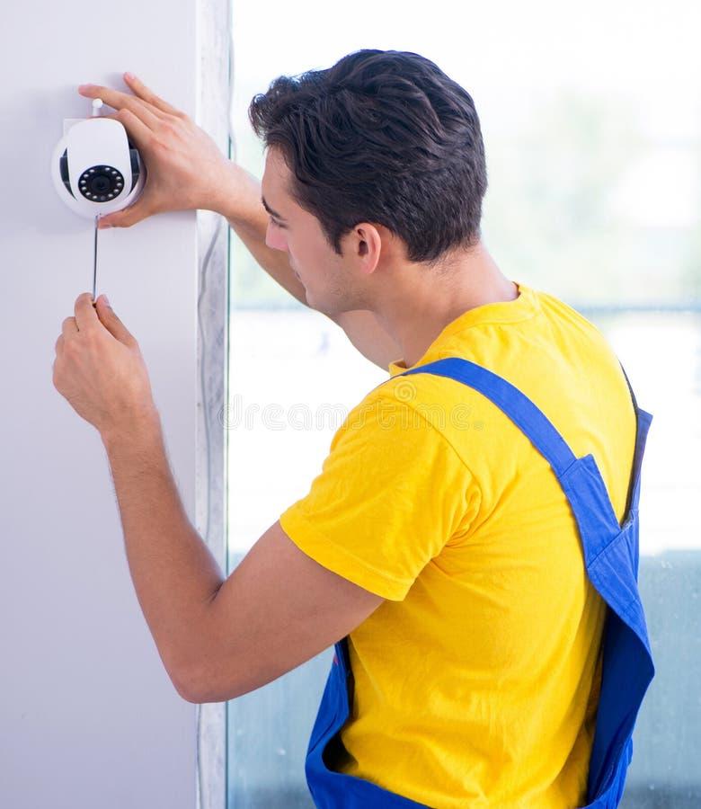 Appaltatore che installa le macchine fotografiche del CCTV di sorveglianza nell'ufficio fotografia stock