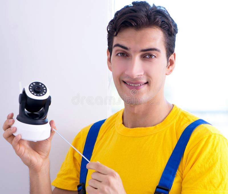 Appaltatore che installa le macchine fotografiche del CCTV di sorveglianza nell'ufficio immagine stock