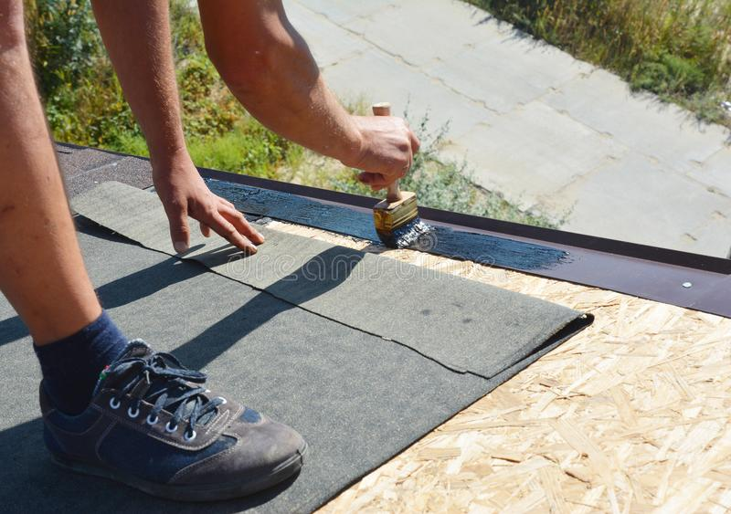 Appaltatore del Roofer che incolla prima membrana impermeabile sulla superficie superiore del tetto di legno con la spazzola e lo fotografia stock libera da diritti