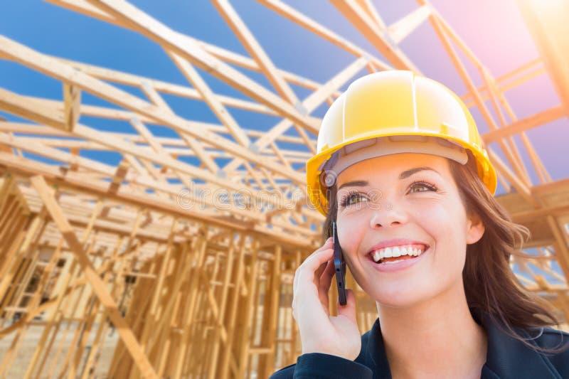 Appaltatore femminile in casco facendo uso del telefono cellulare al cantiere fotografia stock libera da diritti