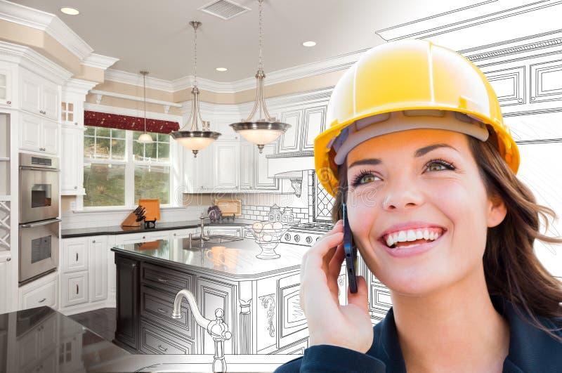 Appaltatore femminile facendo uso del telefono cellulare sopra il disegno della cucina che gradua alla foto fotografia stock