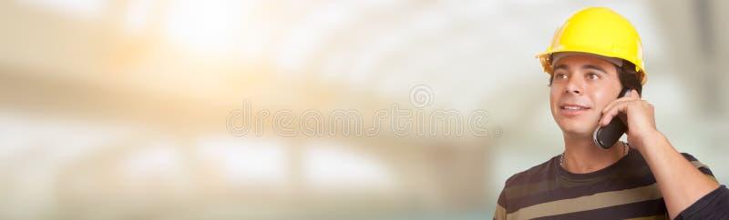 Appaltatore maschio ispano adulto bello in casco facendo uso della cellula P fotografia stock libera da diritti