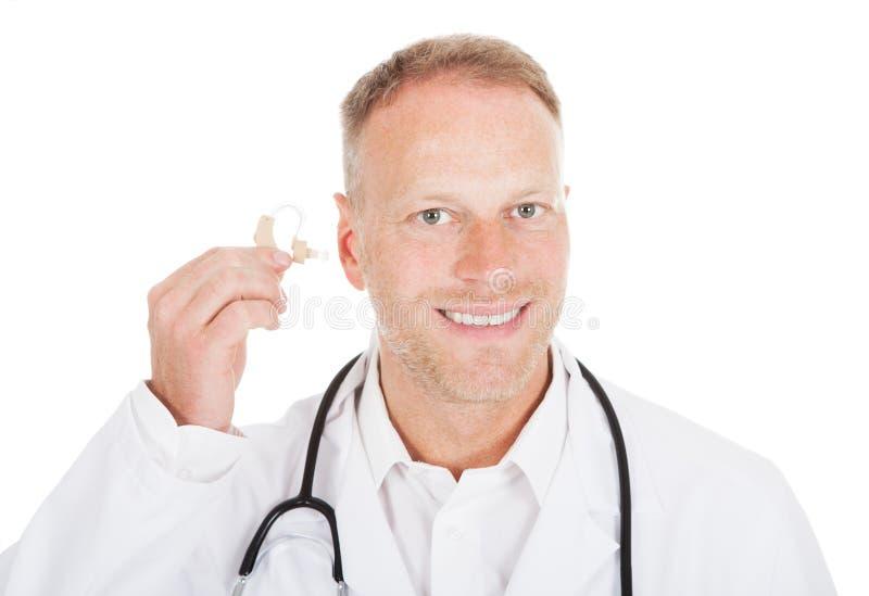 Apparat för doktor Holding Hearing Aid royaltyfria bilder