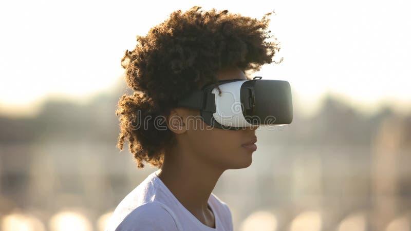 Apparat f?r exponeringsglas f?r virtuell verklighet f?r ung afro--amerikan dam b?rande digital utomhus arkivfoton