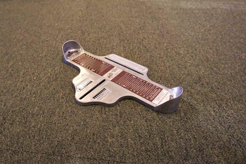 Apparat som mäter fot på matta arkivbild