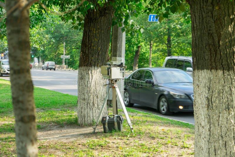 Apparaten för att mäta hastigheten av bilen Polisen som döljas bak ett träd royaltyfria bilder