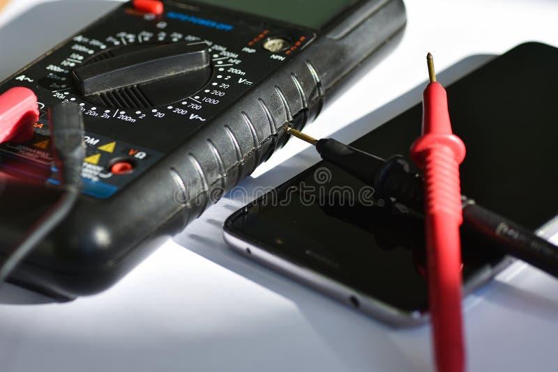 Apparattester för att reparera en defekt smartphone på en vit bakgrund royaltyfri foto