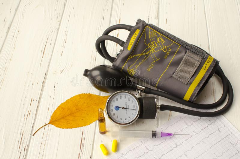 Apparatus for measuring the pressure, cardiogram, syringe, ampoule, pills and dry autumn leaf on white wooden background stock photos