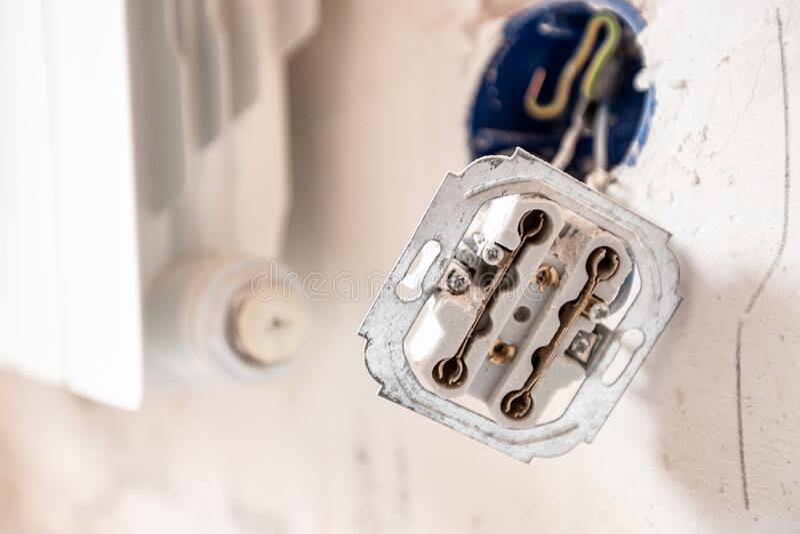 Apparecchiatura elettrica smontata nella parete di detonazione con fili nudi e punzonature durante la riparazione nell'appartamen fotografie stock