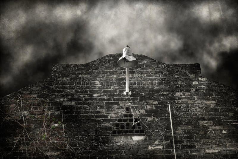 Appareil d'éclairage battu sur un mur de briques image libre de droits